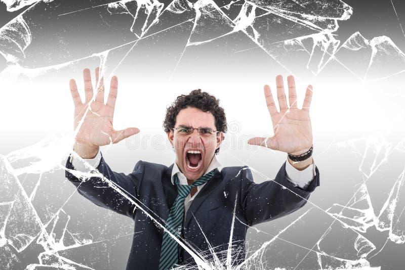 Hombre de negocios enojado y chocado que sostiene la pared de cristal rota imagen de archivo libre de regalías