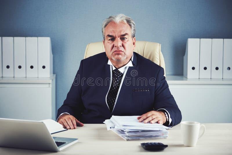 Hombre de negocios envejecido cansado que se sienta en oficina imágenes de archivo libres de regalías