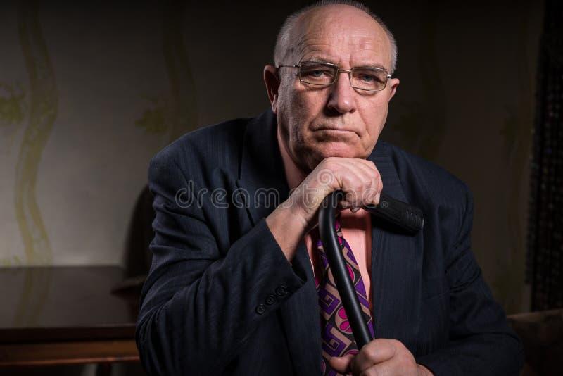 Hombre de negocios envejecido centro serio Holding su bastón imagenes de archivo
