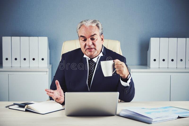 Hombre de negocios envejecido con la taza que habla en el ordenador portátil imagenes de archivo