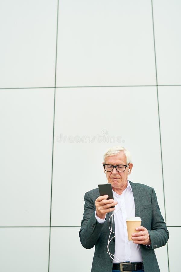 Hombre de negocios envejecido con la taza usando smartphone cerca del edificio foto de archivo libre de regalías