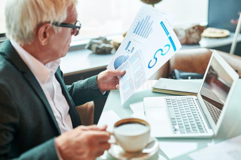 Hombre de negocios envejecido con los papeles de la lectura del café imagen de archivo