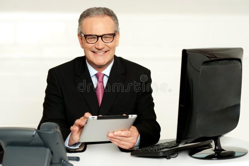 Hombre de negocios envejecido en vidrios usando la tablilla fotos de archivo libres de regalías