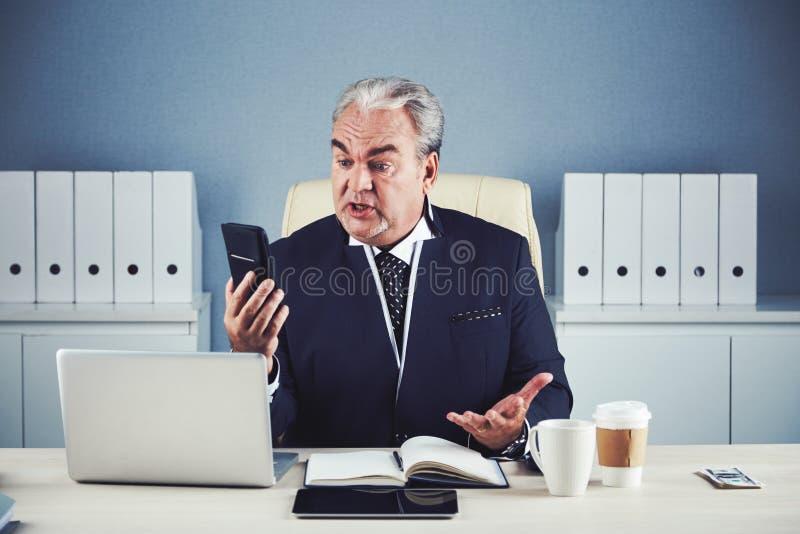 Hombre de negocios envejecido furioso usando smartphone imagenes de archivo