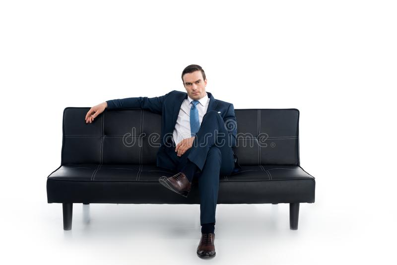 hombre de negocios envejecido medio confiado que se sienta en el sofá y que mira la cámara foto de archivo