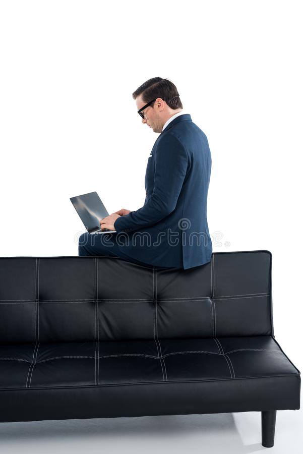 hombre de negocios envejecido medio que se sienta en el sofá y que usa el ordenador portátil foto de archivo libre de regalías