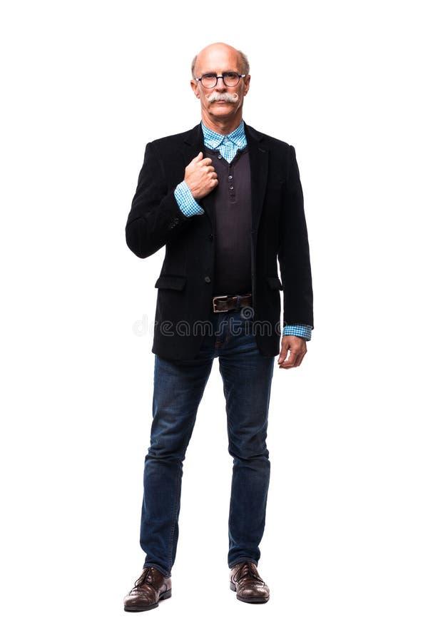 Hombre de negocios envejecido medio sonriente que se coloca con una mano en su bolsillo y la otra que sostiene sus vidrios del oj imagen de archivo libre de regalías