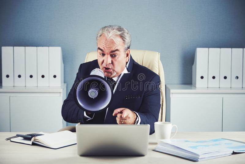 Hombre de negocios envejecido que grita en el megáfono en el ordenador portátil imagenes de archivo