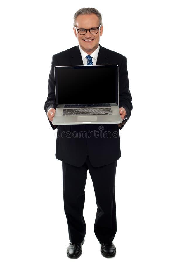 Hombre de negocios envejecido que muestra la computadora portátil nuevamente lanzada imagen de archivo libre de regalías
