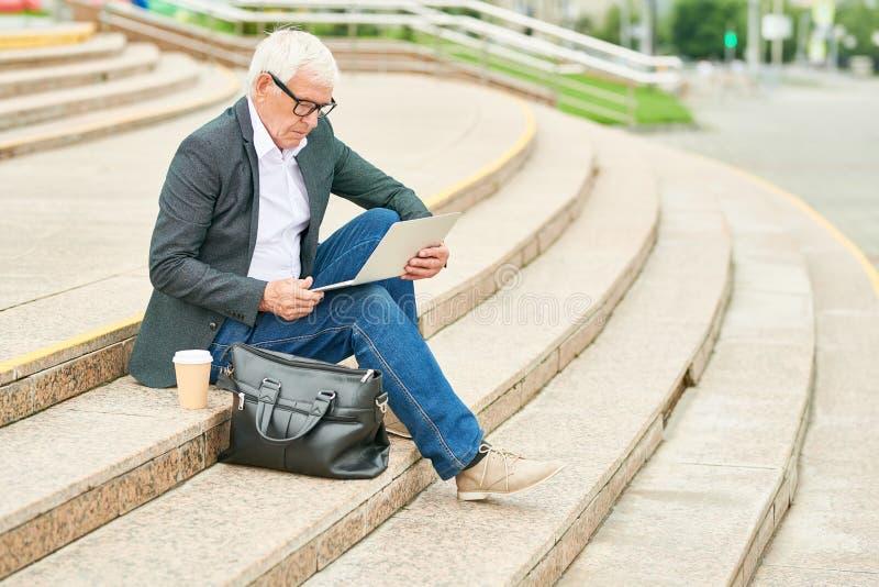 Hombre de negocios envejecido usando el ordenador portátil en las escaleras imagen de archivo libre de regalías