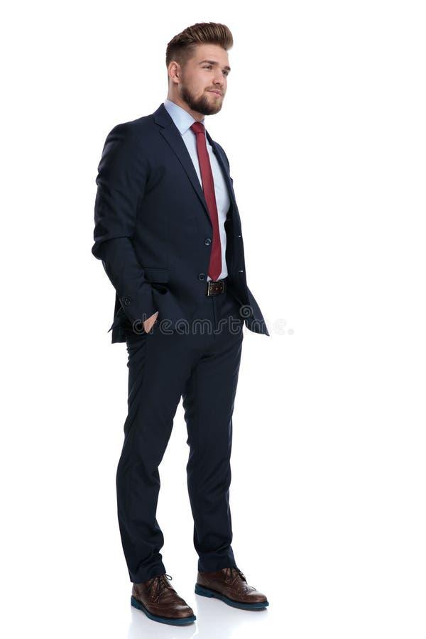 Hombre de negocios esperanzado que lleva a cabo sus manos en sus bolsillos fotografía de archivo