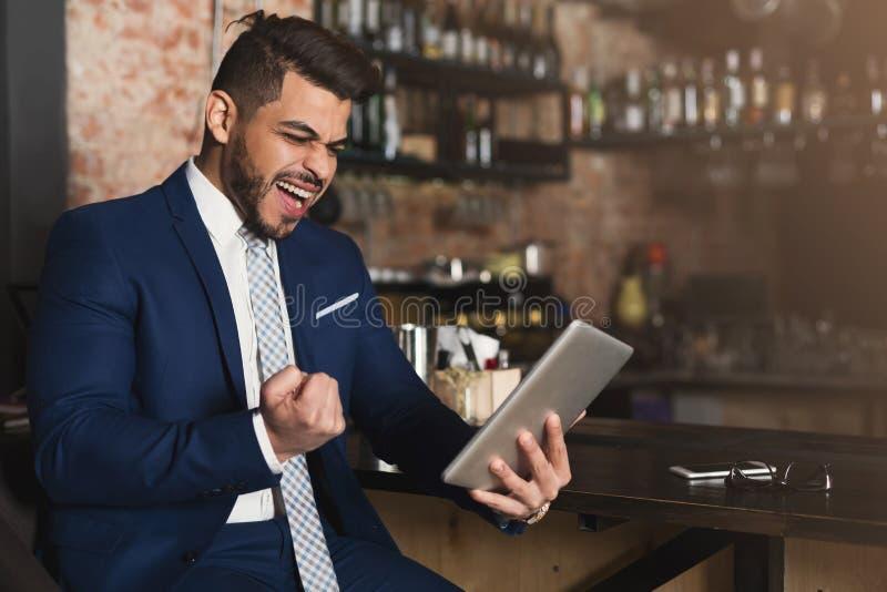 Hombre de negocios eufórico que gana y que mira en la tableta fotografía de archivo libre de regalías