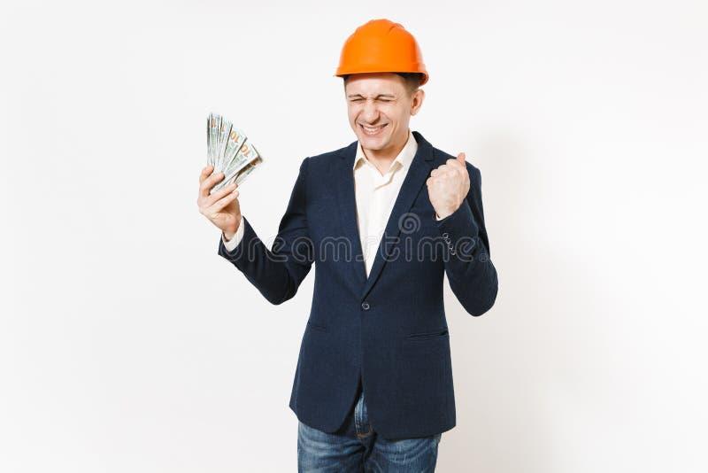Hombre de negocios extático en traje oscuro, paquete protector de la tenencia del casco de protección de dólares, dinero del efec fotos de archivo libres de regalías