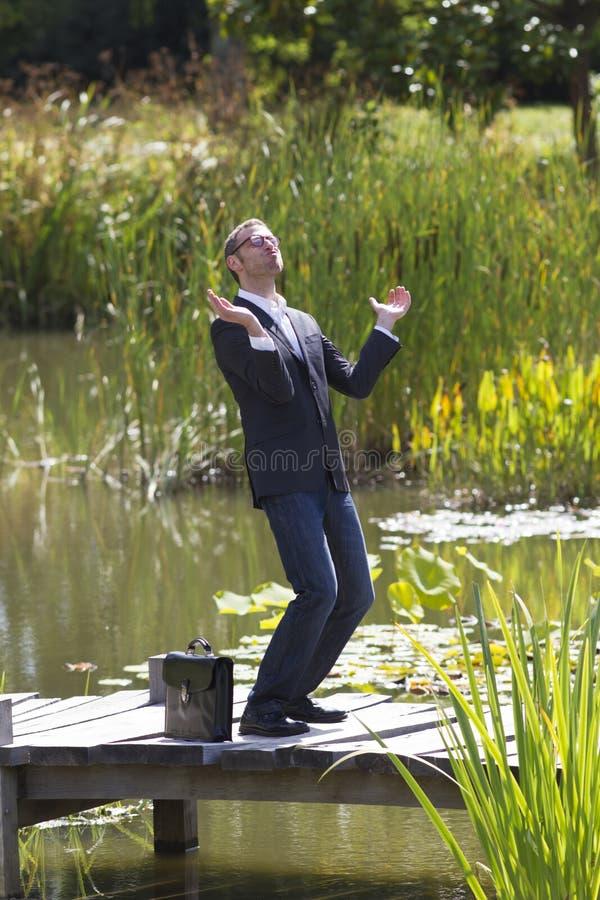 Hombre de negocios extático que aplaude para la promoción del trabajo en el puente cerca del agua foto de archivo libre de regalías