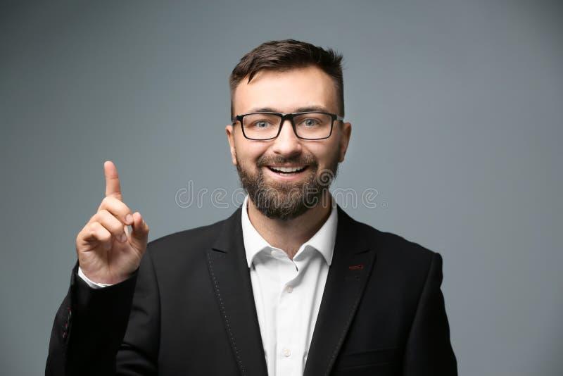 Hombre de negocios feliz con el dedo índice aumentado en fondo ligero fotografía de archivo libre de regalías