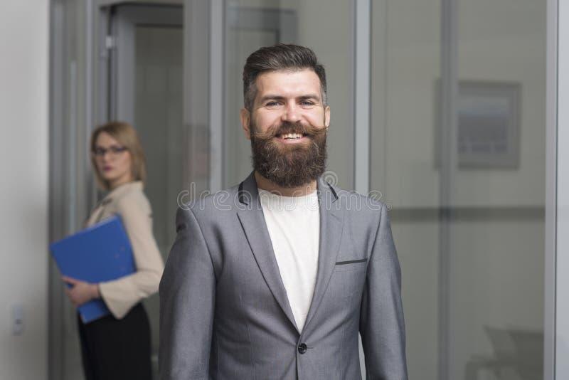 Hombre de negocios feliz con la mujer borrosa en fondo Hombre barbudo en traje formal en oficina Sonrisa confiada del hombre con  imagen de archivo