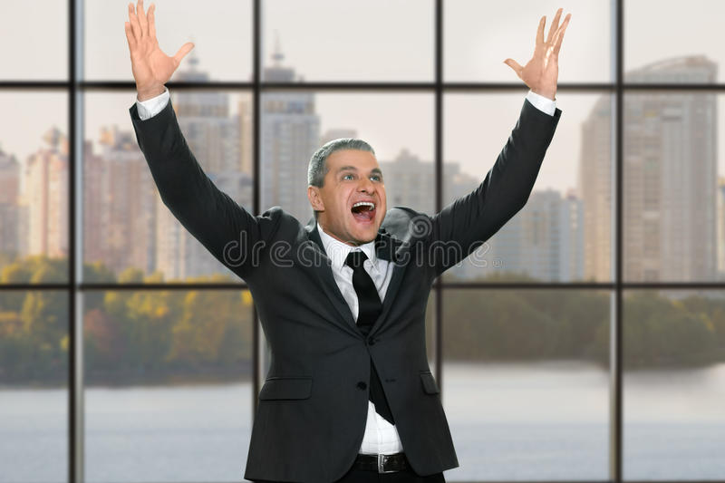 Hombre de negocios feliz con los brazos aumentados imagenes de archivo