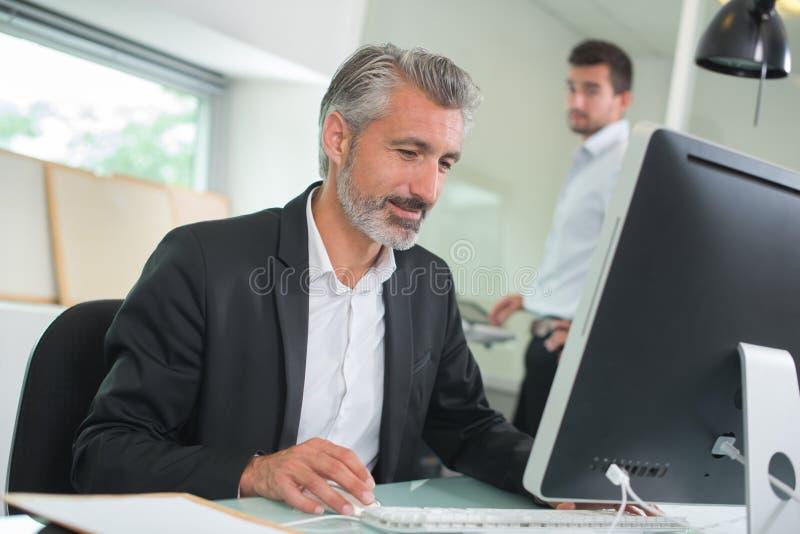 Hombre de negocios feliz confiado usando el ordenador en oficina imagen de archivo libre de regalías