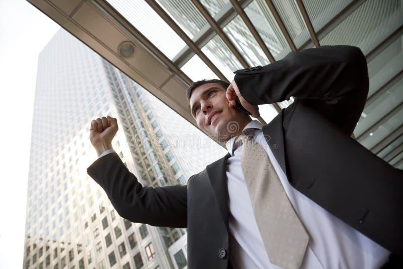 Hombre de negocios feliz de la ciudad que celebra en el teléfono celular imágenes de archivo libres de regalías