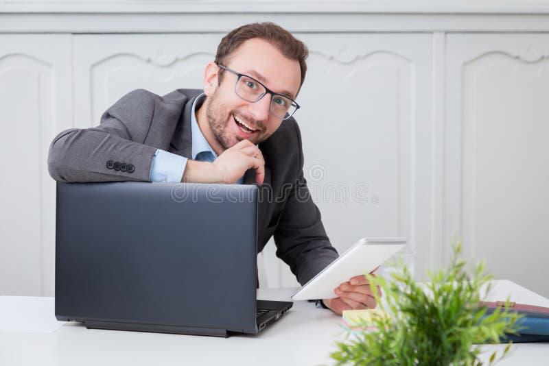 Hombre de negocios feliz en el escritorio de oficina fotografía de archivo