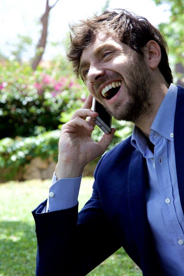 Hombre de negocios feliz en el teléfono en la risa del parque imágenes de archivo libres de regalías