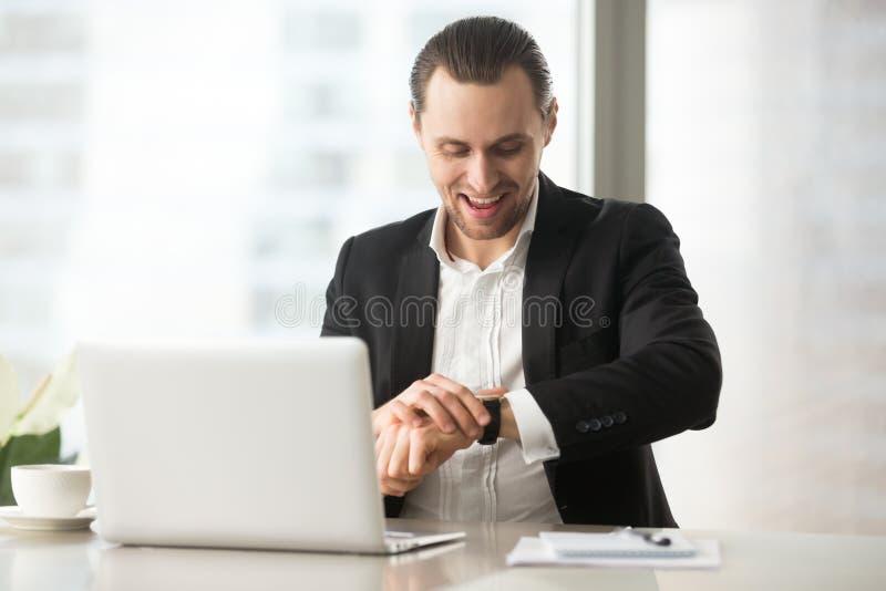 Hombre de negocios feliz en el trabajo que mira el reloj con sonrisa grande fotos de archivo