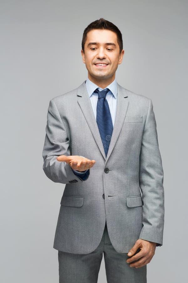 Hombre de negocios feliz en el traje que muestra las palmas vacías fotografía de archivo