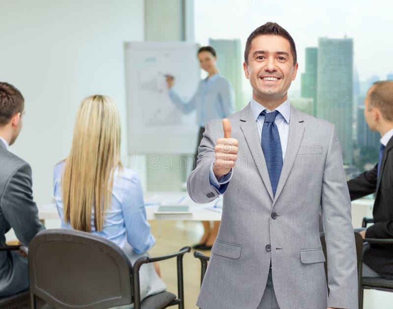 Hombre de negocios feliz en el traje que muestra los pulgares para arriba imágenes de archivo libres de regalías