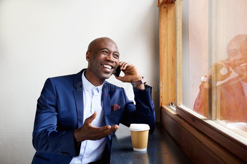 Hombre de negocios feliz en un café que habla en el teléfono celular fotografía de archivo