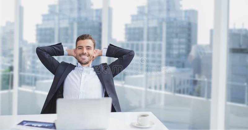 Hombre de negocios feliz en un escritorio que se sienta contra fondo de la ciudad fotografía de archivo
