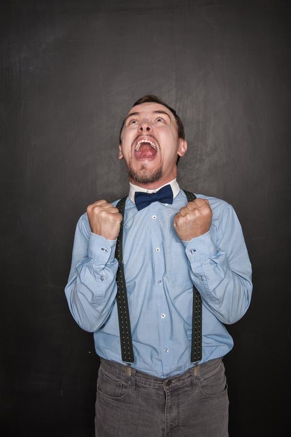 Hombre de negocios feliz de griterío con gesto del sí en la pizarra fotografía de archivo