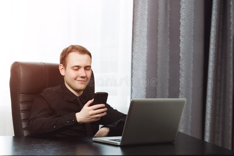 Hombre de negocios feliz hermoso que manda un SMS en su lugar de trabajo fotos de archivo libres de regalías