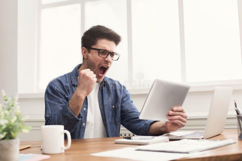 Hombre de negocios feliz joven en oficina con la tableta digital foto de archivo