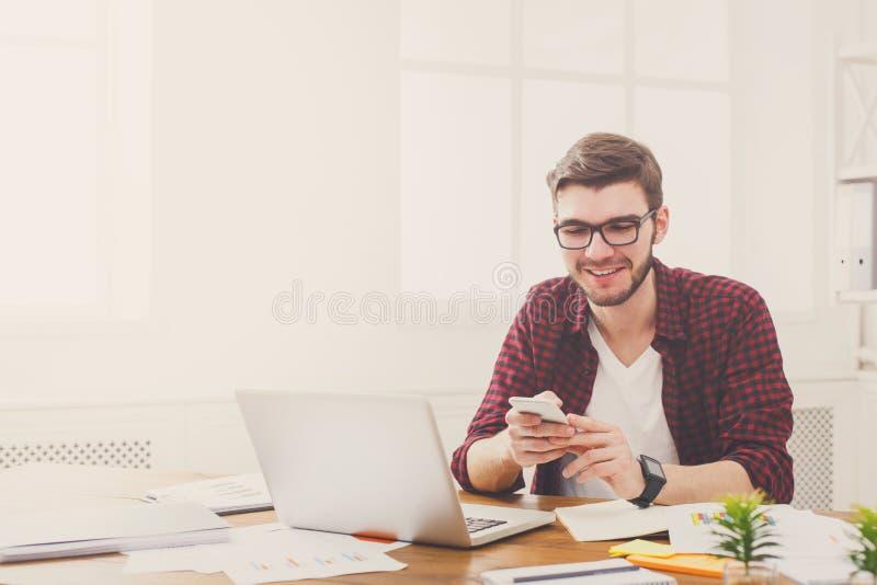 Hombre de negocios feliz joven en oficina usando el teléfono celular por el ordenador portátil imagenes de archivo