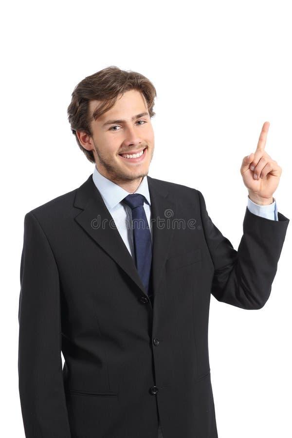 Hombre de negocios feliz joven que señala en el lado y que mira la cámara foto de archivo libre de regalías