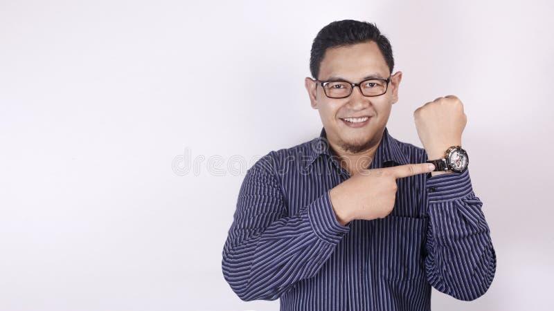 Hombre de negocios feliz Pointing en el reloj foto de archivo libre de regalías