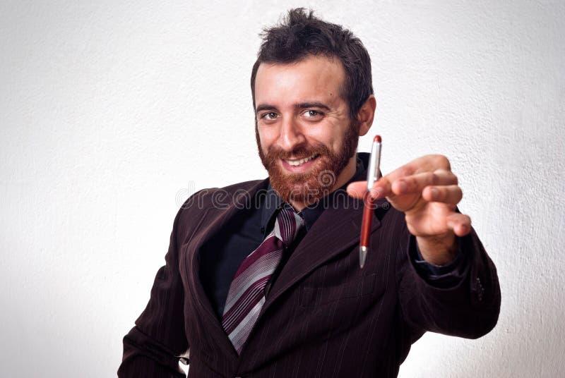 Hombre de negocios feliz que da una pluma para firmar el contrato imágenes de archivo libres de regalías