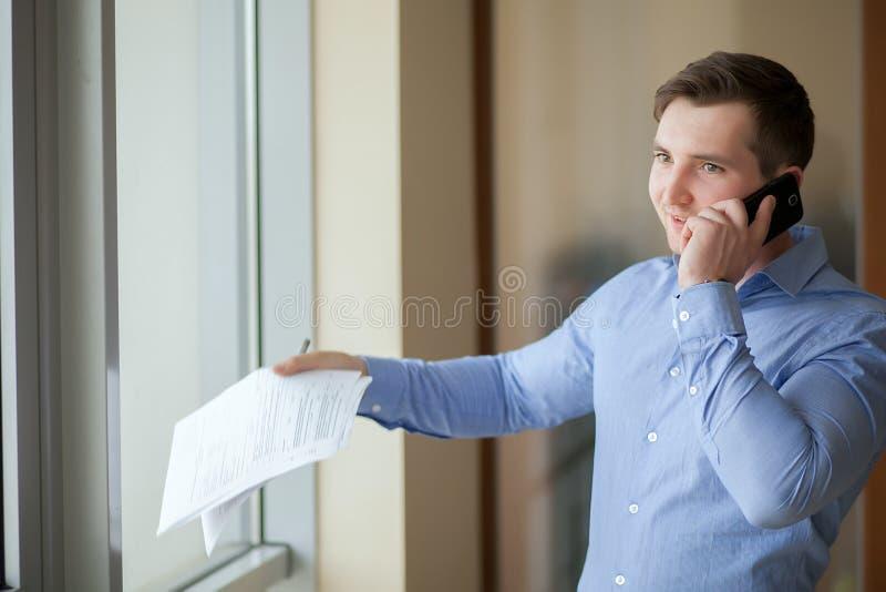 Hombre de negocios feliz que habla en el teléfono en la oficina imagen de archivo libre de regalías