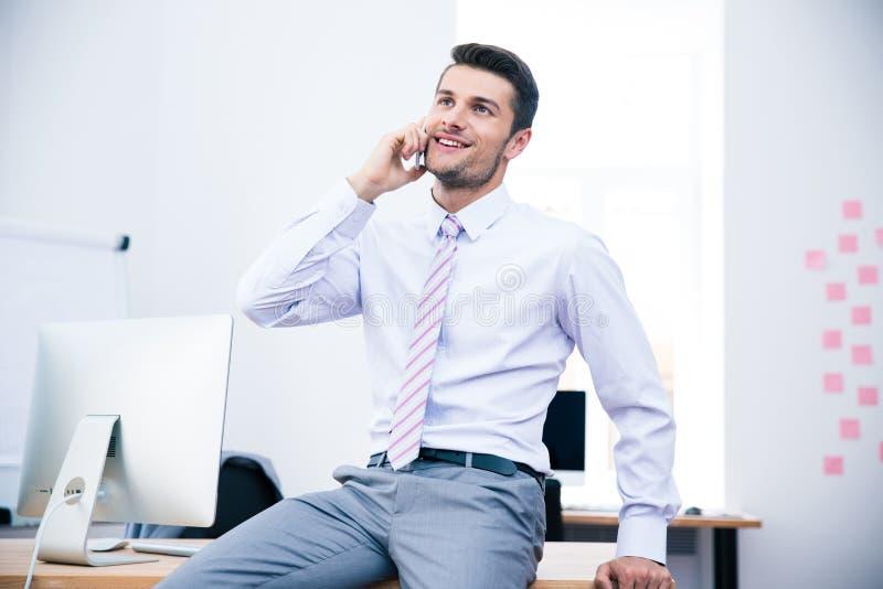 Hombre de negocios feliz que habla en el teléfono en oficina imagenes de archivo