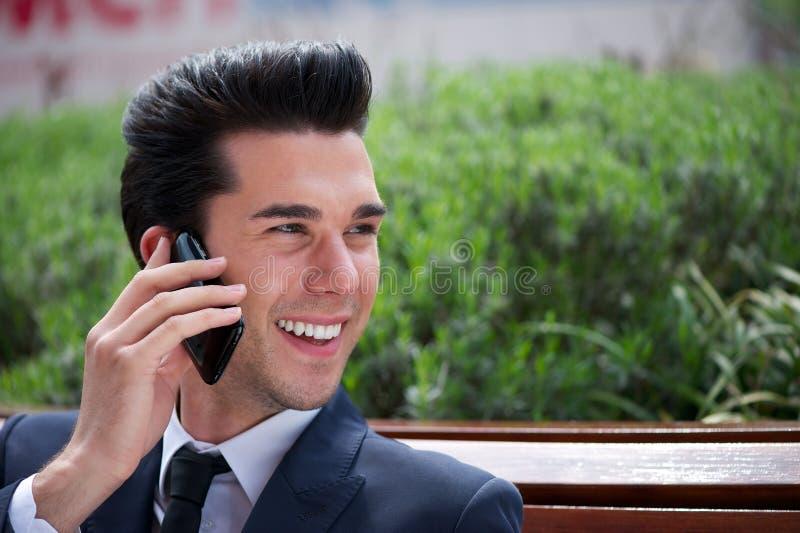 Hombre de negocios feliz que habla en el teléfono fuera de la oficina fotos de archivo