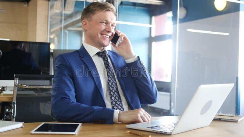 Hombre de negocios feliz que habla en el teléfono móvil en oficina imagenes de archivo