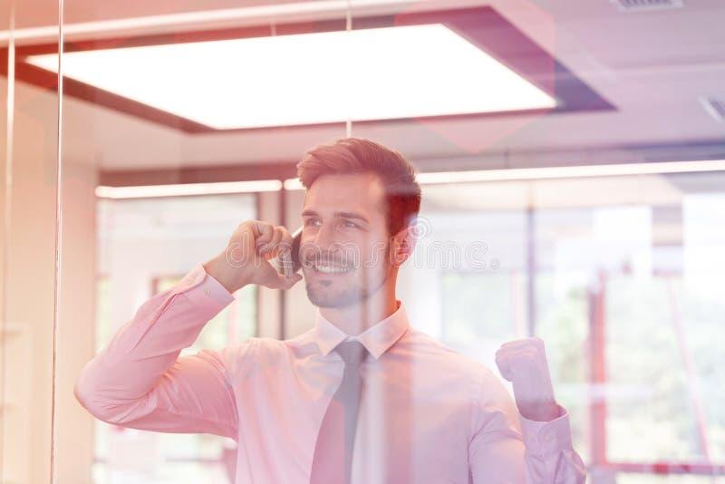 Hombre de negocios feliz que habla en a trav?s ventana vista smartphone en la oficina fotos de archivo libres de regalías