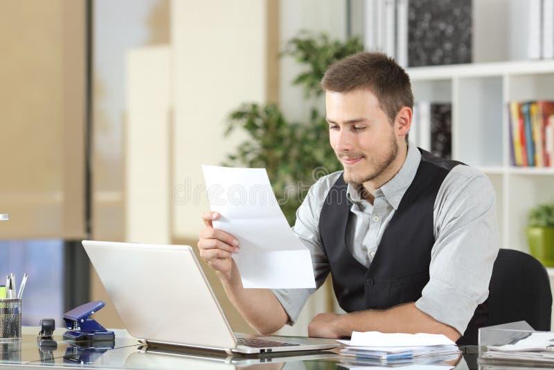 Hombre de negocios feliz que lee una letra en la oficina imagen de archivo libre de regalías