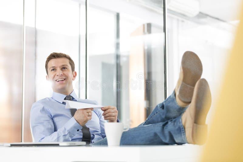 Hombre de negocios feliz que lleva a cabo el avión del papel en oficina imagen de archivo