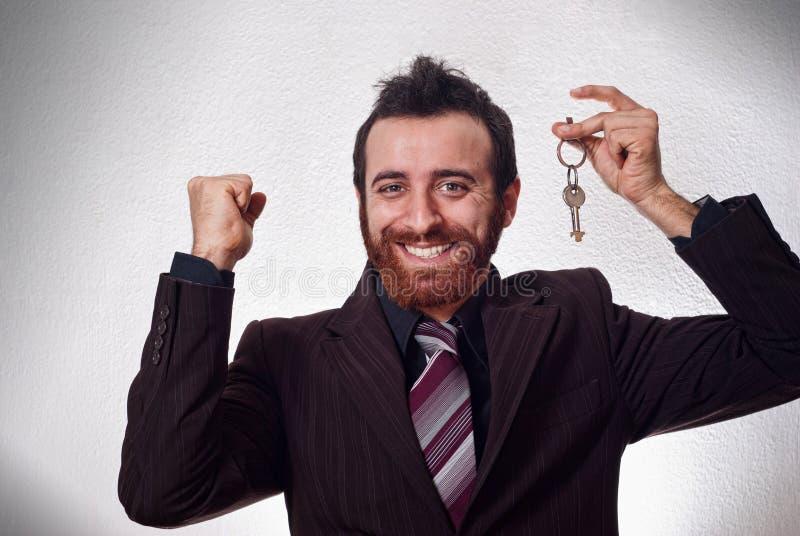 Hombre de negocios feliz que lleva a cabo una llave de la casa imágenes de archivo libres de regalías