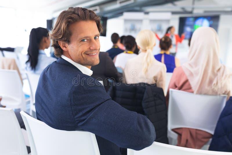 Hombre de negocios feliz que mira la cámara durante seminario del negocio foto de archivo