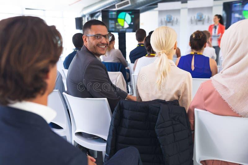 Hombre de negocios feliz que mira la cámara durante seminario del negocio fotografía de archivo