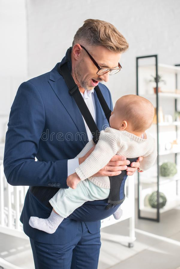 hombre de negocios feliz que mira a la hija pequeña foto de archivo