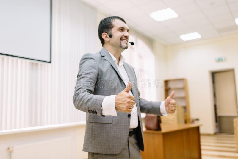 Hombre de negocios feliz que muestra los pulgares para arriba en el fondo de la oficina Concepto del éxito de asunto foto de archivo libre de regalías