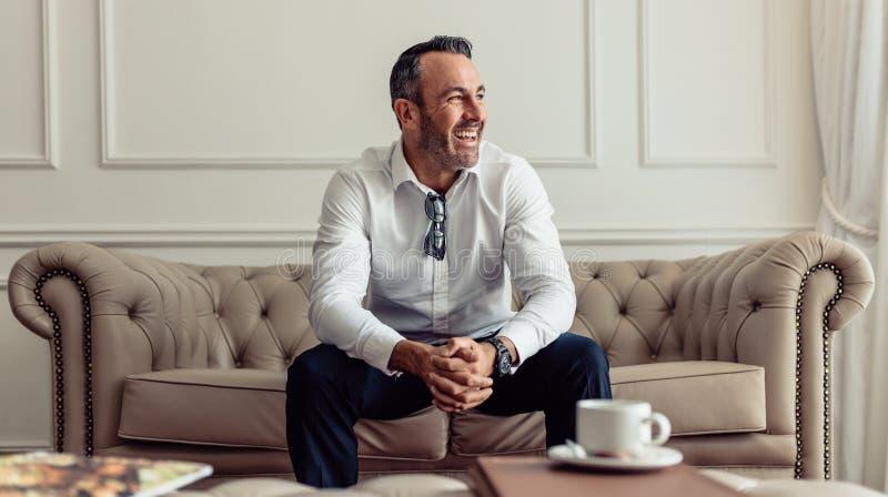 Hombre de negocios feliz que permanece en una habitación fotos de archivo